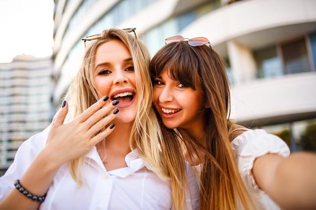Due belle bionde bacchetta donna abilità positive sorelle donna che fa selfie in strada, colori soleggiati estivi, camicie bianche emozioni uscite.