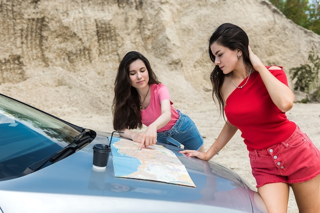 도로 여행에서 잃어버린 차 근처에서지도를 읽고 두 예쁜 백인 여성 드라이버