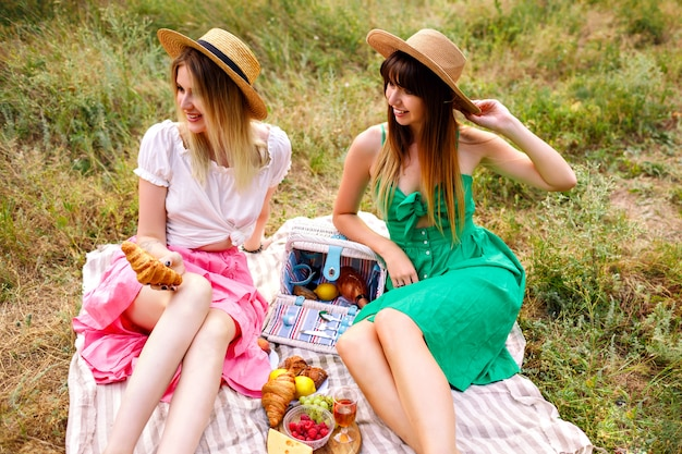 Two pretty cheerful best friends woman, wearing matching romantic elegant dresses and straw hats