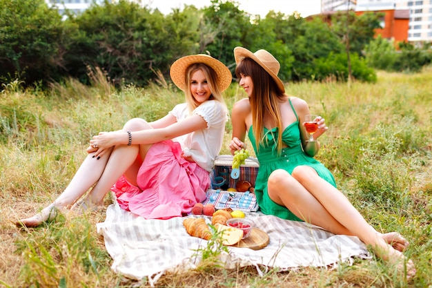 Two pretty cheerful best friends woman , wearing matching romantic elegant dresses and straw hats