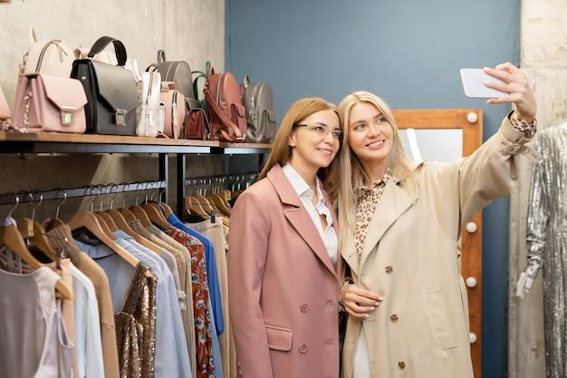 부티크에서 옷을 입고 선반 사이에 서있는 동안 셀카를 만드는 새로운 트렌디 한 코트를 입은 두 명의 꽤 쾌활한 여성