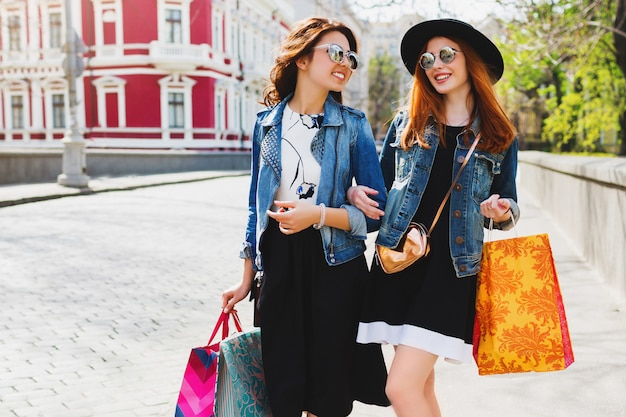 Two pretty cheerful women shopping in city, walking in the streets