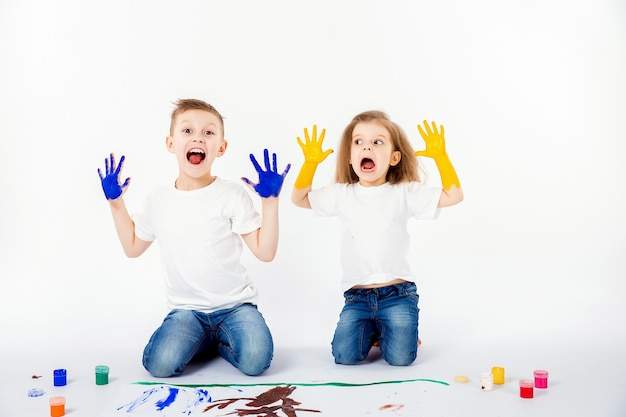 Two pretty child friends boy and girl are drawing pictures by paints. showing hands in paint