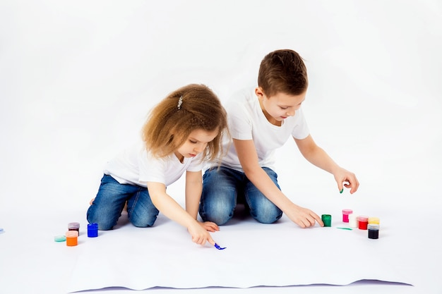 Two pretty child friends boy and girl are drawing pictures by paints