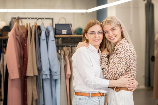 ブティックや衣料品部門のカメラの前に立って抱き合っている2人のきれいな女性客