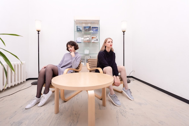 ミニマルなインテリアの部屋でテーブルのそばに座っている2人のかわいい女子学生。