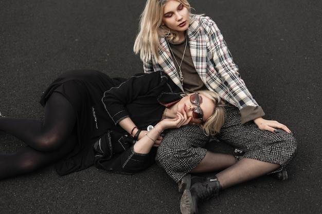 Two pretty fine sisters in fashionable clothes resting on basketball court in city