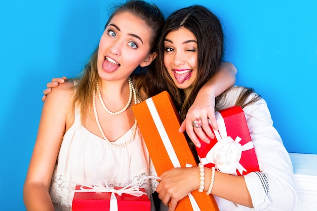 Two pretty friends girls holding bright holiday presents