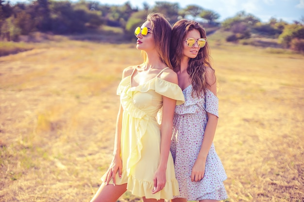 Two pretty girlfriends in summer dresses