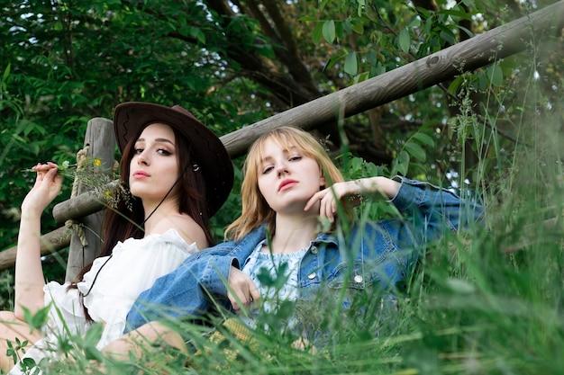 2人のかわいい女の子が白いフェンスの下の背の高い草に座っています。西洋のコンセプト。ソフトフォーカス。女性と自然。