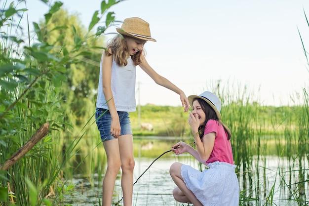 葦の湖の木製の桟橋に座って、水で遊んで、話している、後ろ姿の2人のかわいい女の子の子供たち。夏休み、自然、幸せな子供時代、友情、カントリースタイル。