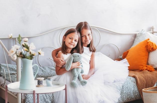 두 명의 예쁜 여자가 침대에서 껴안는 다. 작은 자매들은 밝은 방에 앉아 있습니다. 아이들의 우정