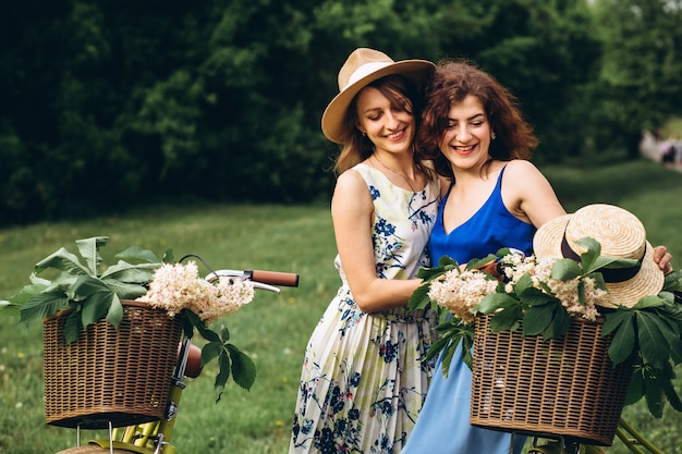 2人のかわいい女の子が日没で春の公園で自転車で行きます。ガールフレンドは楽しんで、笑って、笑って、自転車に乗る。ドレスと麦わら帽子の2人の若い女性のポートレート、クローズアップ。夏のアクティブな休日