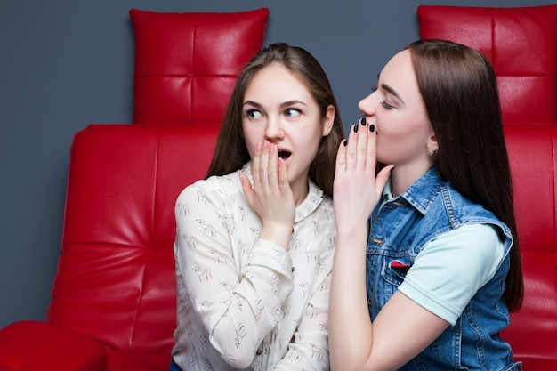 Two pretty girls gossiping on red leather couch. women secrets