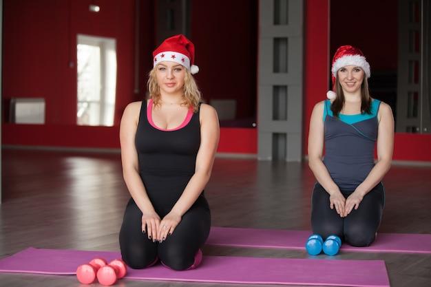 Две красивые девушки в шляпах санта-клауса сидят на ковриках в фитнес-центре