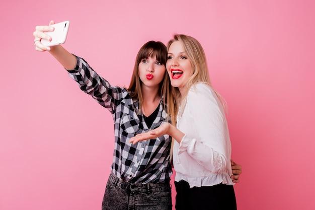 携帯電話でセルフポートレートを作る2つのかわいい女の子