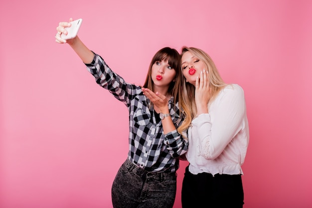 Two pretty girls making self portrait by mobile phone