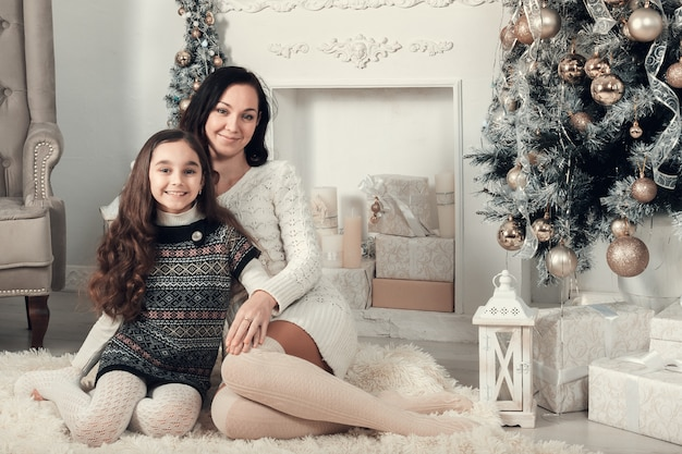 Two pretty girls, mother and daughter siting on a floor in christmas decorated room.