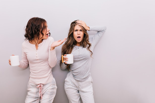 Two pretty girls in pajamas fooling around on gray wall . they having fun together.