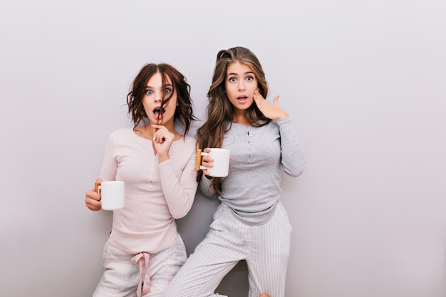 Two pretty girls in pajamas fooling around on gray wall . they having fun .
