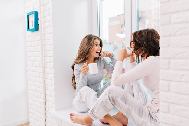 Two pretty girls in pajamas sitting on window in light room. they drinking tee, girl with long hair looks astonished outside window.