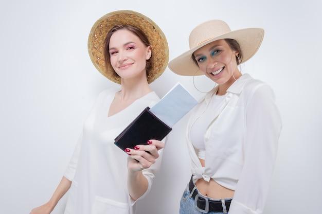 Две красивые девушки позируют на белом фоне перед поездкой. концепция туризма. смешанная техника