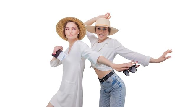Две красивые девушки позируют на белом фоне перед поездкой. концепция туризма.