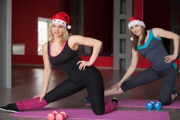 Two pretty girls in santa claus hats exercise on mats in fitness center