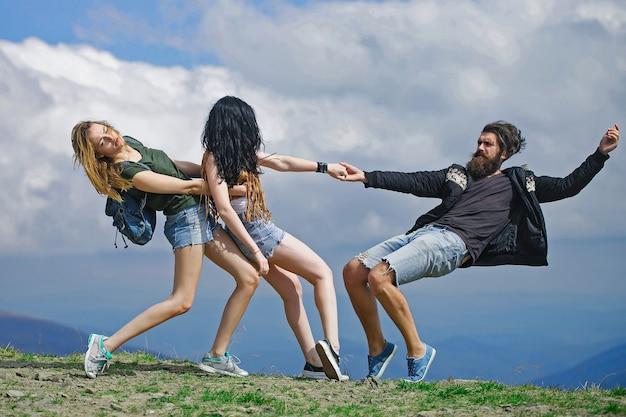 Две красивые девушки стройные модели тянут бородатого мужчину-хипстера на вершине горы в пасмурное небо