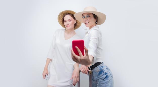 Две симпатичные девушки делают селфи на фоне белой стены перед тем, как отправиться в путешествие. концепция туризма. смешанная техника