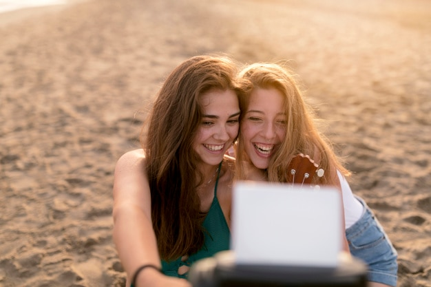 Two pretty girls taking instant photograph from camera at beach