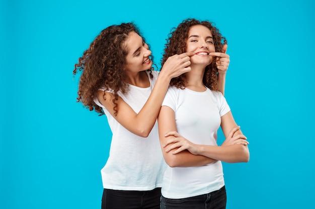 Две красивые девушки-близнецы улыбаются, шутя над синей стеной