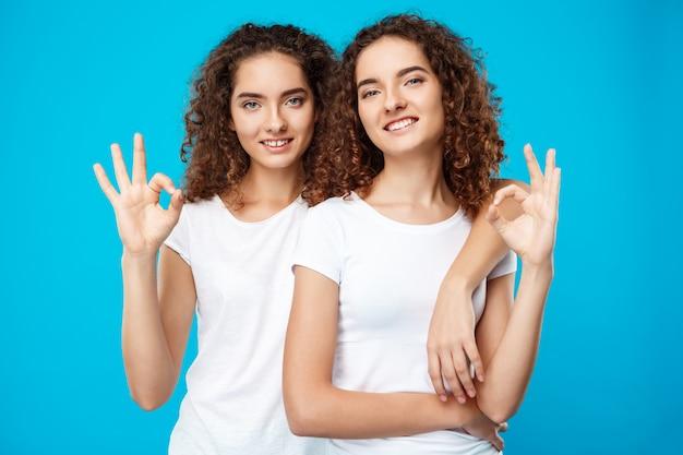 Две красивые девушки-близнецы улыбаются, показывая хорошо над синей стеной