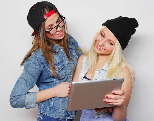 격리되지 않은 흰색 배경 위에 태블릿으로 자화상을 찍는 두 명의 예쁜 힙스터 소녀