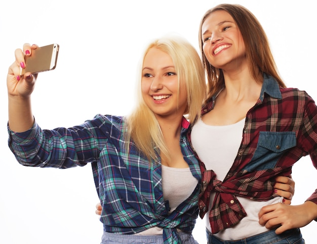 셀카를 찍는 두 명의 예쁜 힙스터 소녀. 흰색 배경에 고립.