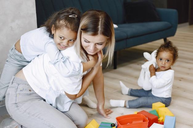두 명의 예쁜 아이들과 그들의 금발 엄마는 바닥에 앉아서 소파 근처에서 장난감을 가지고 노는 아프리카계 미국인 자매들이 집에서 놀고 있습니다