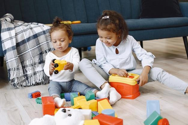두 예쁜 아이가 바닥에 앉아 소파 근처에서 장난감을 가지고 놀아요. 집에서 놀고있는 아프리카 계 미국 흑인 자매.