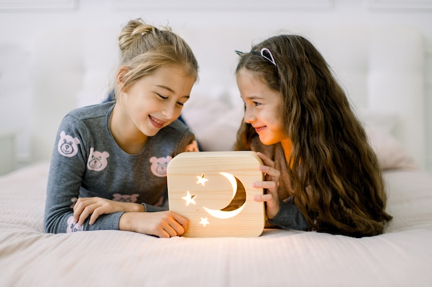 Two pretty little girls sisters, lying on bed at home and enjoying their time playing with wooden night lamp with moon and stars picture.