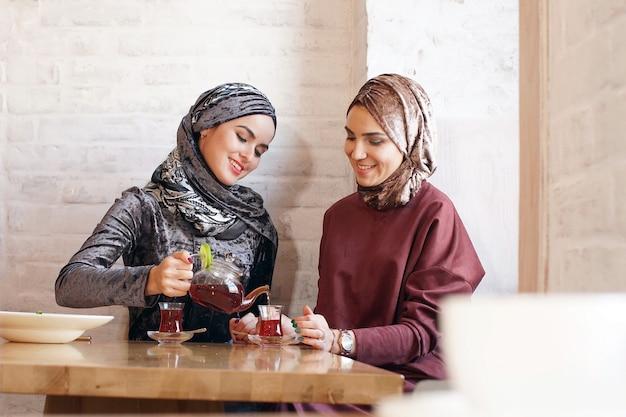 Two pretty muslim women in hijabs drink tea in cafe