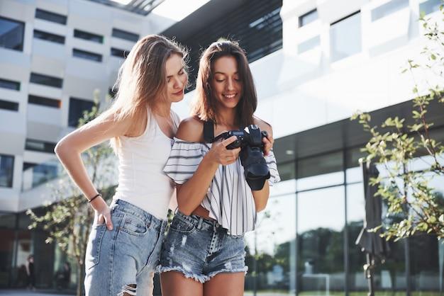 Две милые подружки девушки с камерой фотографируют вместе и гуляют по городу