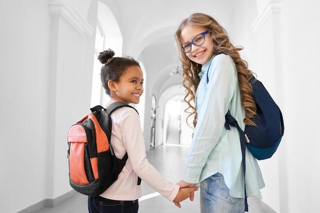 Две симпатичные школьницы блондинка кавказская и брюнетка африканская держатся друг за друга за руки и улыбаются