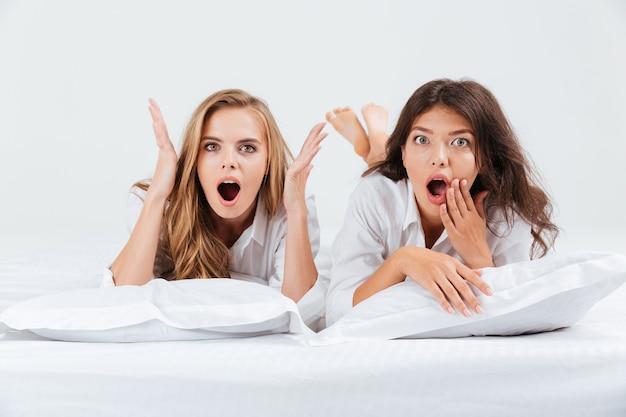 Две довольно шокированные женщины в рубашках лежат на белой кровати с подушками и смотрят в камеру