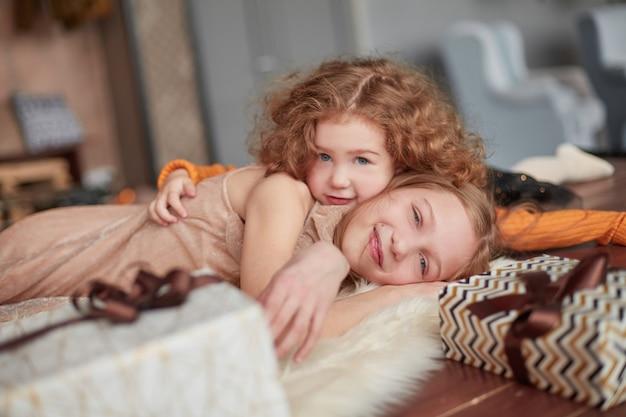 예쁜 두 자매가 아늑한 거실에서 즐거운 시간을 보내고 있습니다.