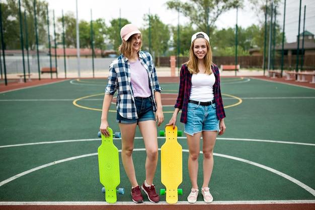 2人のかわいい笑顔のブロンドの女の子が手に明るいロングボードを持ってスポーツフィールドに立っています