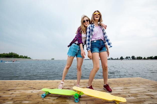 市松模様のシャツとデニムのショートパンツを着た2人のかわいい笑顔のブロンドの女の子が桟橋に立っています