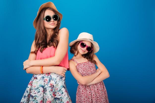 Две довольно улыбающиеся сестры стоят и позируют со сложенными руками на синем фоне