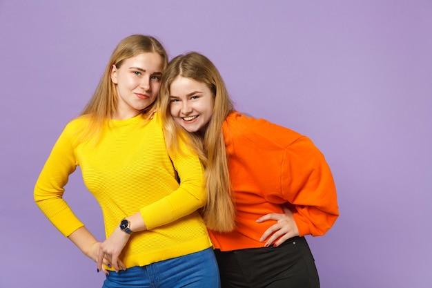 두 꽤 웃는 젊은 금발 쌍둥이 자매 소녀 서, 파스텔 바이올렛 파란색 벽에 고립 된 생생한 화려한 옷을 입고. 사람들이 가족 라이프 스타일 개념.