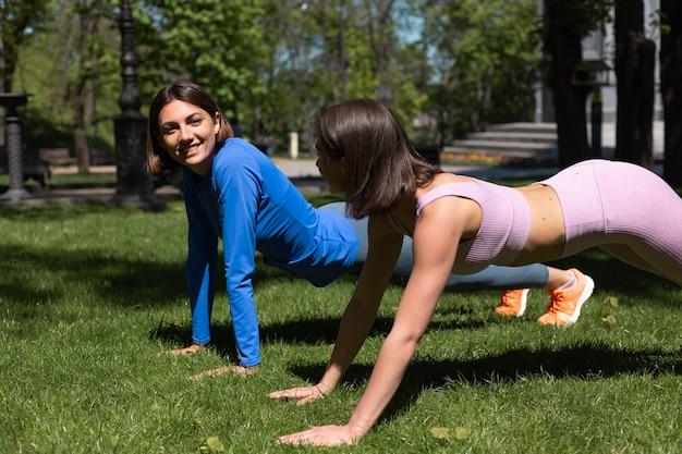 晴れた日に公園の芝生の上でスポーツウェアの2人のきれいな女性がトレーニングプラントをやってお互いに幸せな感情をサポートしています