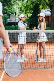 두 명의 예쁜 여자가 클레이 코트에서 테니스 복식을 하고 있습니다.