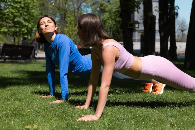 Two pretty woman in sport wear on grass in park at sunny day doing workout plant support each other happy emotions
